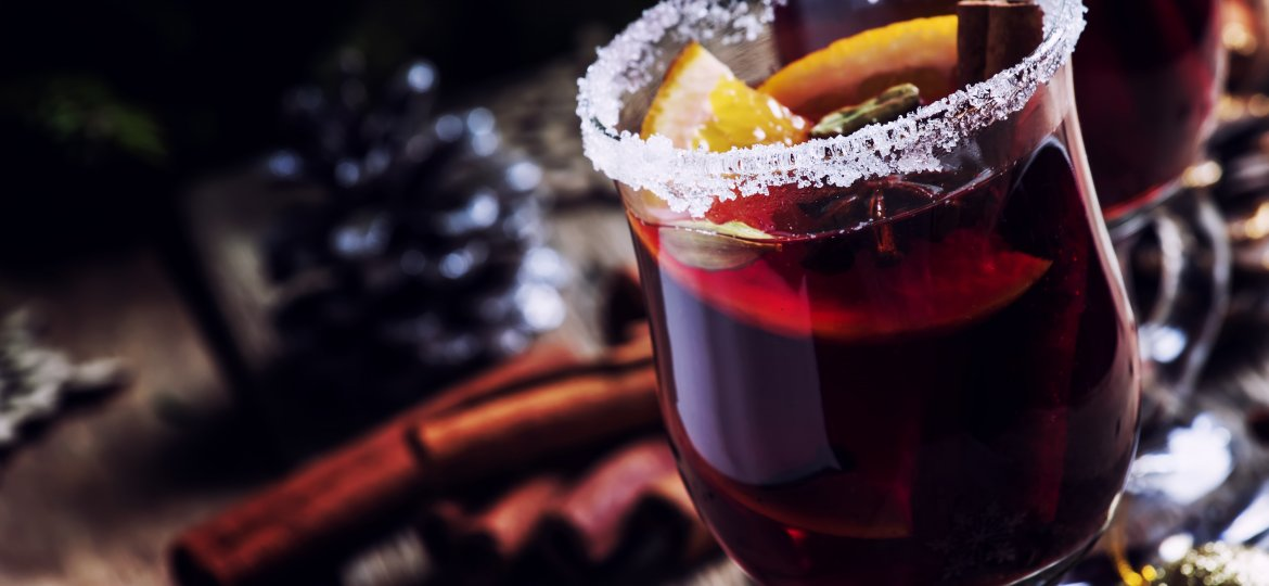Christmas and New Year festive drink, hot mulled wine with cinnamon, cardamom, orange and anise star on background of green spruce branches and lights, rustic wooden table, selective focus